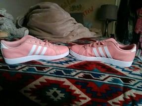 pair of pink addidas low-top sneakers