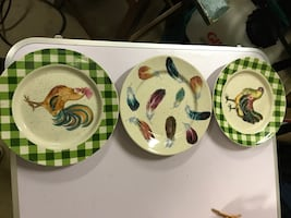 Three white-and-green chicken decorative plates with display rack