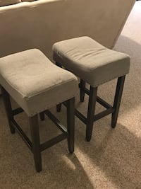 Two light gray padded low bar stools
