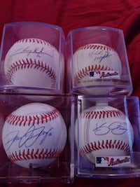 four signed white-and-red baseballs