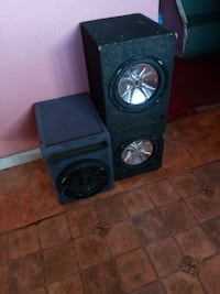 three black and gray subwoofers with enclosures
