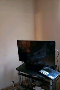 black flat screen TV with remote Framingham, 01701