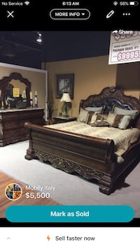 brown wooden bed frame with white mattress Laval