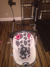 white, black, and gray floral Graco portable swing