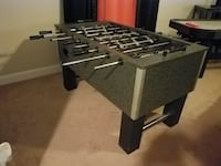 Gray and black foosball table, air hockey games