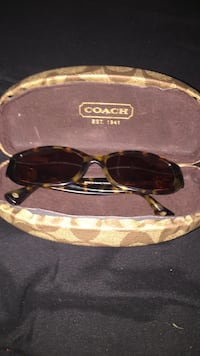 brown and black framed Coach sunglasses with case