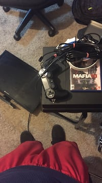 black Sony PS4 console with controller and game cases Rogers, 72758