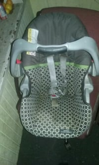 baby's gray, green, and black car seat carrier