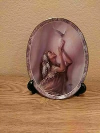 woman in brown dress holding white bird decorative plate