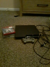 black Sony PS3 slim console with controller