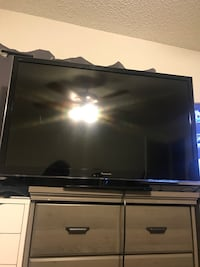 black flat screen TV with black Tv Stand , Panasonic. 42""