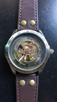 Silver and gold skeleton watch with brown leather band.
