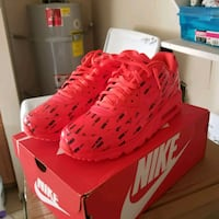 pair of red Nike cleats on box