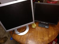two white and black flat screen computer monitors