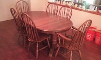 oval brown wooden table with six windsor chair set
