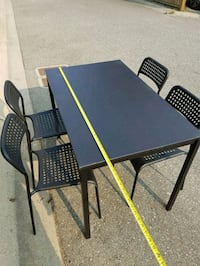 rectangular black wooden table with four chairs di Surrey, V4N 5P9