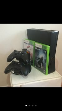 Black xbox 360 console with controllers and two games