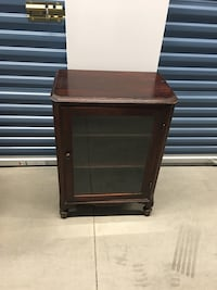 Small wooden cabinet with glass door