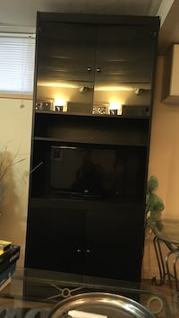 black wooden TV hutch with black flat screen television