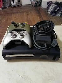 black Xbox 360 console with two controllers