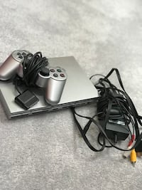 grey Sony PS2 with controller and black AC adapter