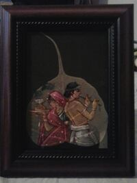 brown wooden framed painting of male and female