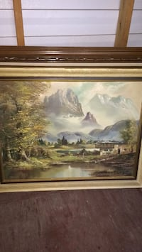 Brown wooden framed painting of house near body of water