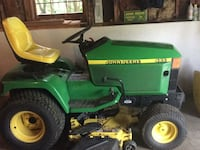 green and yellow John Deere ride on lawn mower