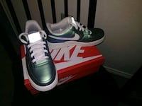 pair of green Nike low-top sneakers with box