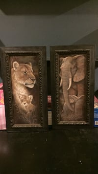 two black framed lioness and elephant paintings