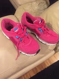 Pair of pink nike running shoes and sperry shoes