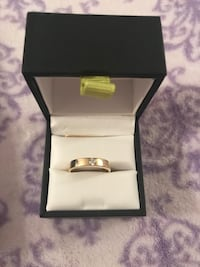 silver-colored ring with clear gemstone and box