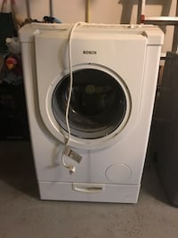 White Bosch front-load dryer and grey Whirlpool Duet dryer.