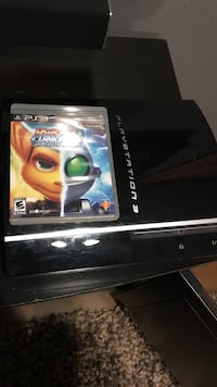 black Sony PS3 game console with game cases