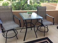 black metal framed glass top patio table with chairs