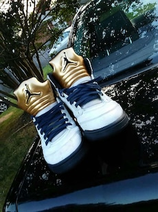 white-and-gold colored Air Jordan basketball shoes