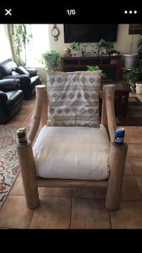 Brown wooden framed beige padded armchair