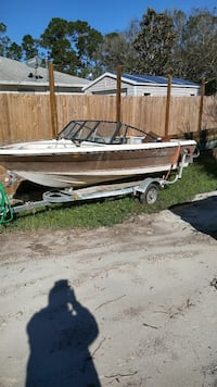 brown and white speed boat with boat trailer