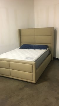 Beige queen bed with pillowtop mattress. Floor model