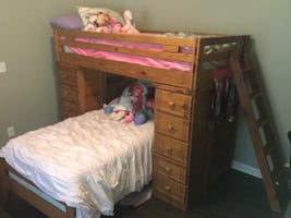 Brown wooden bunk bed with mattress and box spring.