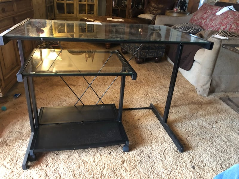 Computer table with roll away matching stand. Doesn't take up much space. Is in great condition .Black metal frame, and glass tops. 65c32a12-ddd8-4583-9b26-41764b9088d1
