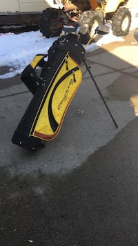 Black and yellow stand golf bag with golf clubs