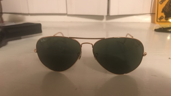 black Ray-Ban Aviator sunglasses with gold frame