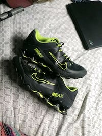 pair of black-and-green Nike cleats 492 mi