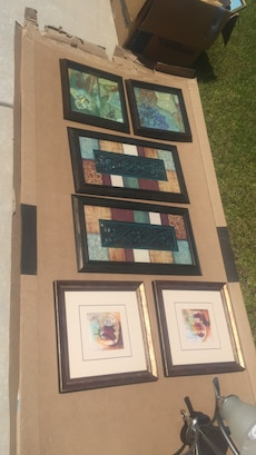 assorted paintings with wooden frames
