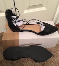 pair of black pointed flat shoes with box