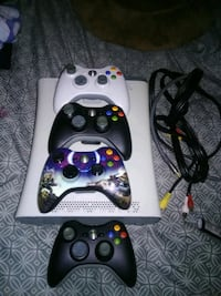 Xbox 360 game console plus four remote controls and all the cords