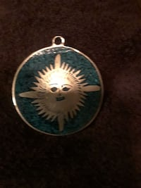 blue and silver-colored sun print pendant