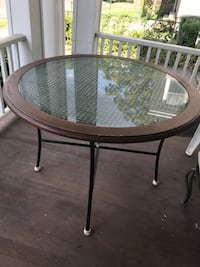 Round brown wooden framed glass-top table