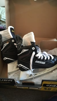 White and black leather bauer ice skates on box